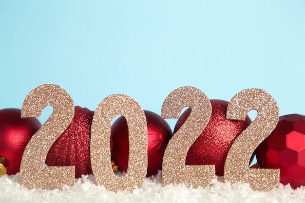 Fundo de natal com bolas de natal e numerais 2022. conceito de ano novo em azul.