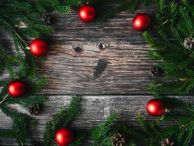 Fundo de natal com bolas vermelhas, ramos de abeto e pinhas