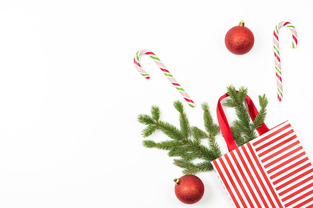 Fundo de natal com bolsa de presente, galho de árvore do abeto, decoração, bastões de doces em branco