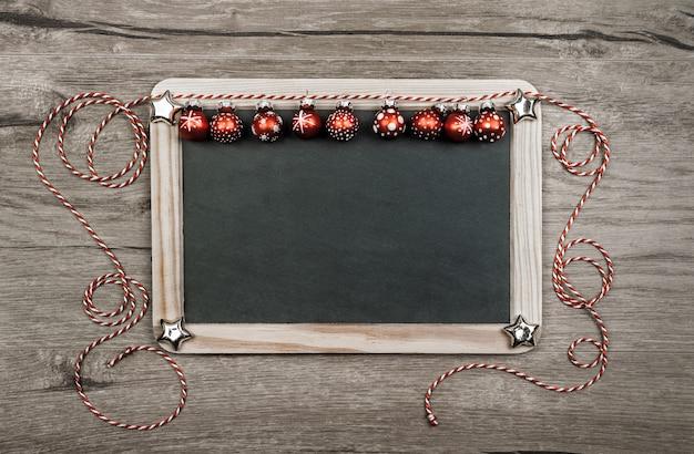 Fundo de natal com bugigangas vermelhas, espaço de texto no quadro-negro