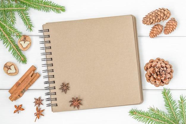 Fundo de natal com caderno, cones de galhos de árvore de natal e especiarias