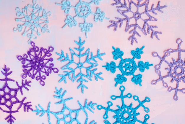Fundo de natal com caderno em branco, floco de neve de malha azul, feito à mão em um fundo roxo-rosa. tendência de papel rasgado. vista plana leiga, superior. copyspace.