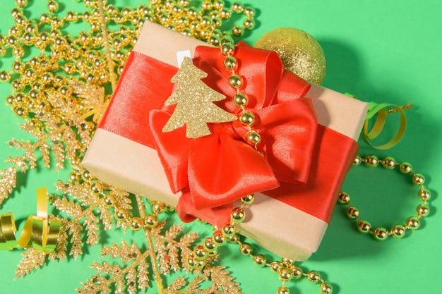 Fundo de natal com caixa de presente com laço de fita vermelha na decoração festiva dourada sobre fundo verde.