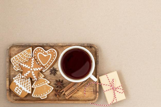 Fundo de natal com caixa de presente de biscoitos de gengibre e uma xícara de chá