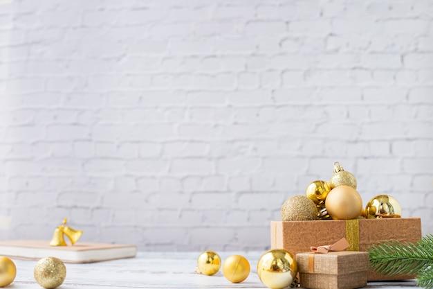 Fundo de natal com caixa de presente de ouro bauble na textura da parede de tijolo branco