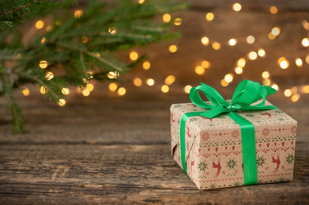 Fundo de natal com caixa de presente galho de árvore de natal e luzes desfocadas