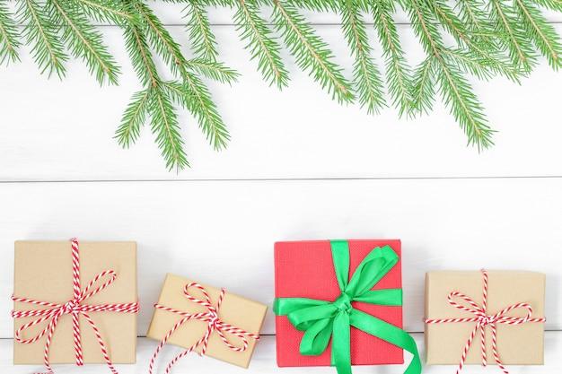 Fundo de natal com caixas de presente e galhos de árvore de natal em uma superfície de madeira