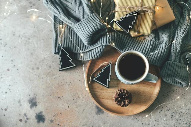 Fundo de natal com caneca de café, suéter aconchegante, guirlanda de luzes, presentes e decoração festiva