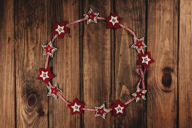 Fundo de natal com coroa de estrelas vermelha.
