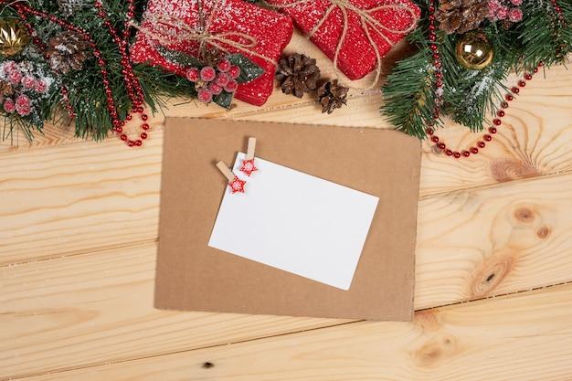 Fundo de natal com decoração e cartão de natal, bagas vermelhas, ramo de abeto e vista superior de presentes