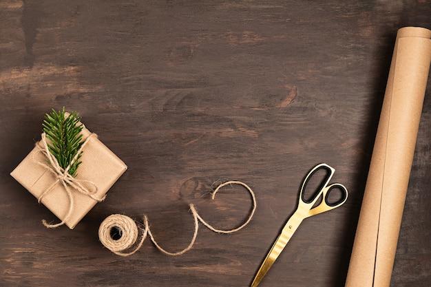 Fundo de natal com embrulho de presentes artesanais, apresenta-se na mesa de madeira rústica. embalagem de natal diy.