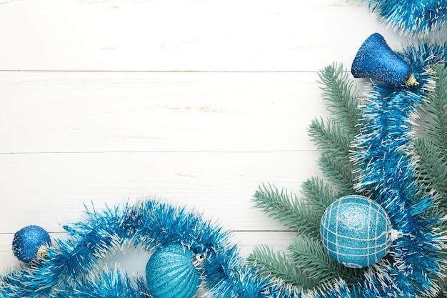Fundo de natal com enfeites azuis em fundo branco de madeira. vista do topo.