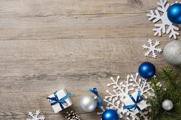 Fundo de natal com enfeites e caixas de presente branca com fita azul na mesa de madeira.