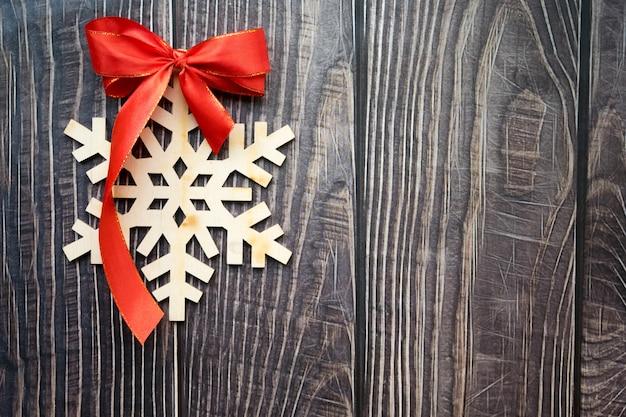 Fundo de natal com floco de neve de madeira e laço vermelho na prancha de madeira velha