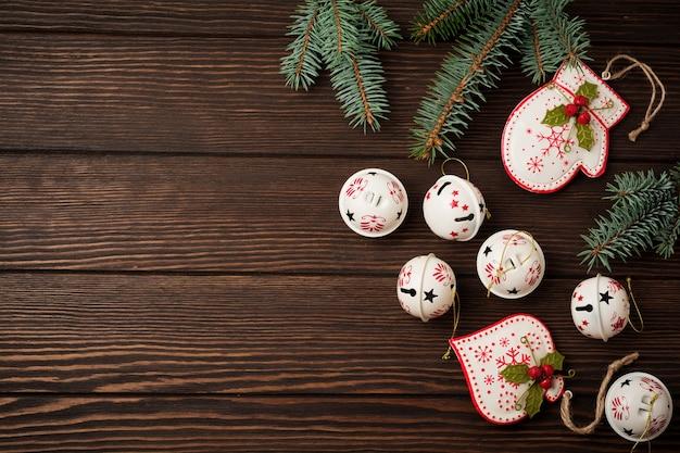 Fundo de natal com galhos de pinheiro, brinquedos e sinos na mesa de fundo de madeira velha. foco seletivo. vista superior com espaço de cópia.