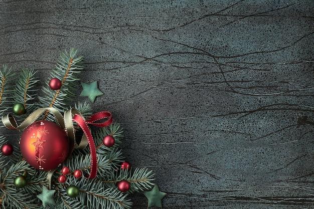 Fundo de natal com galhos de pinheiro e bugigangas de vidro em verde e bordô no escuro, cópia-espaço