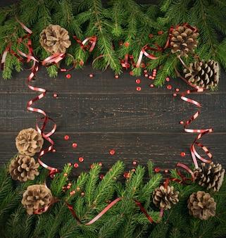 Fundo de natal com galhos de pinheiro e pinhas na mesa de madeira