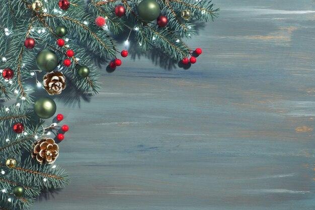 Fundo de natal com galhos de pinheiro, frutas vermelhas, cones e luzes de natal em madeira rústica verde