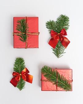 Fundo de natal com galhos de pinheiro verde decorados e caixa de presente vermelha em branco.
