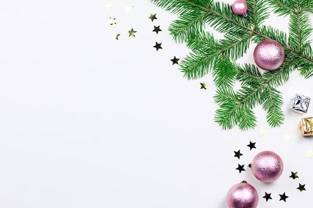 Fundo de natal com galhos de pinheiros, luzes de natal, enfeites rosa e bege, enfeites de prata