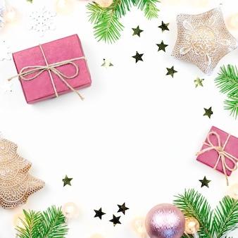 Fundo de natal com galhos de pinheiros, luzes de natal, presentes, enfeites rosa e bege, enfeites de prata
