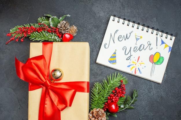 Fundo de natal com lindos presentes com fita em forma de arco e acessórios de decoração de ramos de abeto e caderno em uma mesa escura acima da vista