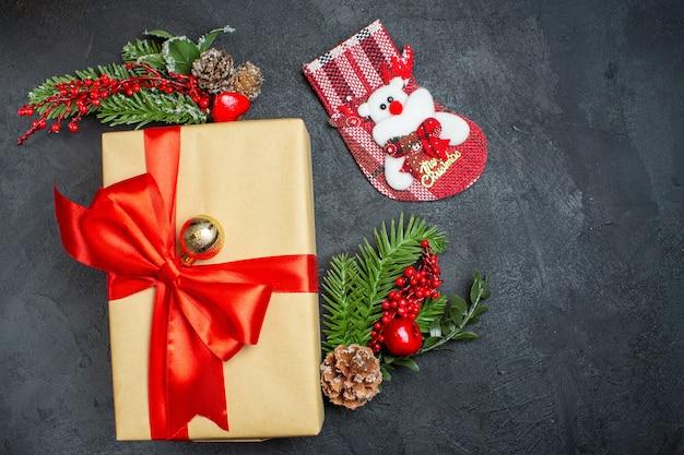 Fundo de natal com lindos presentes com fita em forma de arco e acessórios de decoração de ramos de abeto meia de natal em uma mesa escura v
