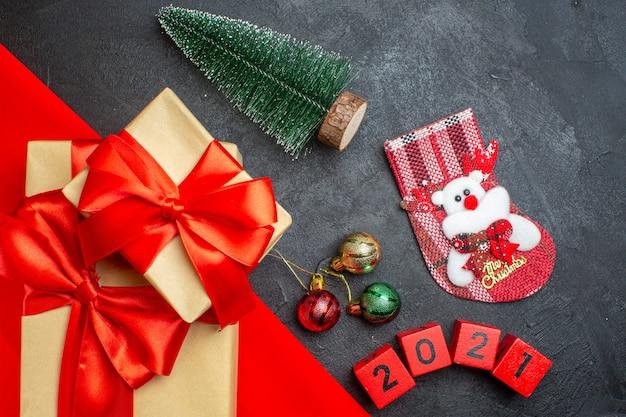 Fundo de natal com lindos presentes com fita em forma de arco em uma toalha vermelha e acessórios de decoração de meias xsmas em uma mesa escura