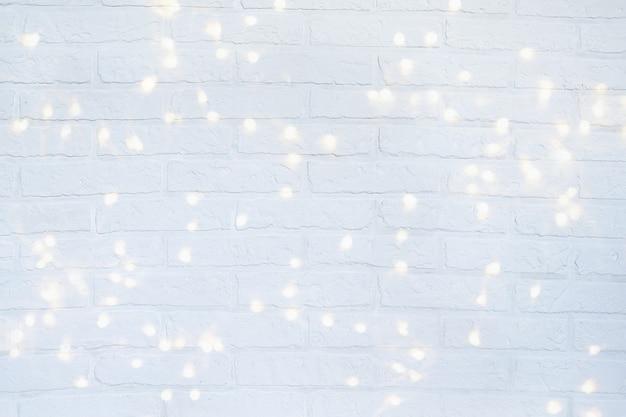 Fundo de natal com luzes brilhantes. parede de tijolos brancos.