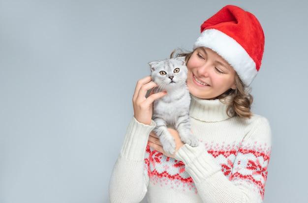 Fundo de natal com menina adolescente sorridente com chapéu de papai noel e gatinho