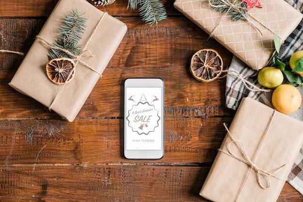 Fundo de natal com página inicial da loja online na tela do smartphone, caixas embaladas e embrulhadas e clementinas