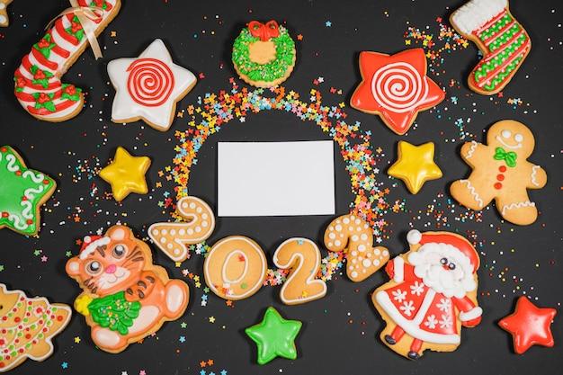 Fundo de natal com pão de gengibre na superfície cinza do cartão de visita do feriado humor vista superior