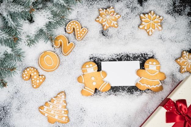Fundo de natal com pão de mel na neve do inverno. cartão de humor de férias. vista superior, copie o espaço. tradições familiares, diy, conceito de celebração. fundo festivo com biscoitos caseiros de gengibre.