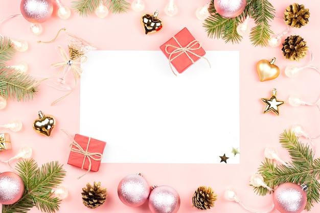 Fundo de natal com papel em branco, presentes, galhos de árvore do abeto, decorações douradas em rosa. copie o espaço