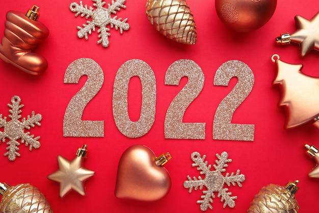 Fundo de natal com pinheiros, cones de abeto e decorações de natal e algarismos 2022. conceito de ano novo em vermelho. vista do topo