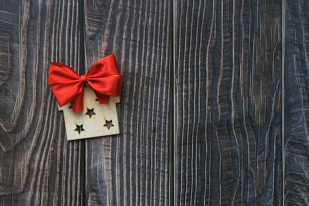 Fundo de natal com presente decorativo de madeira e laço vermelho na prancha de madeira velha