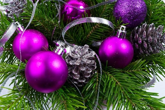 Fundo de natal com ramo de abeto verde e ornamentos roxos