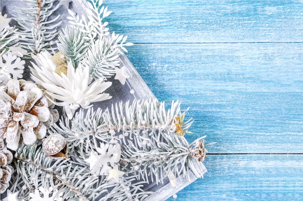 Fundo de natal com ramos de abeto branco e flocos de neve em um fundo azul de madeira