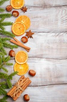 Fundo de natal com ramos de abeto, nozes, especiarias e laranjas secas.