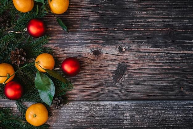 Fundo de natal com tangerinas, ramos de abeto, bolas vermelhas e pinhas na mesa de madeira.