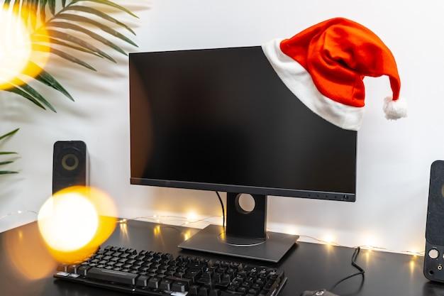Fundo de natal com tela de computador com chapéu e espaço de cópia para texto