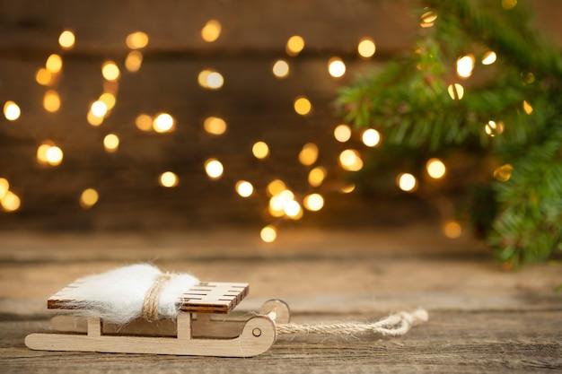 Fundo de natal com trenó e luzes desfocadas em fundo de madeira