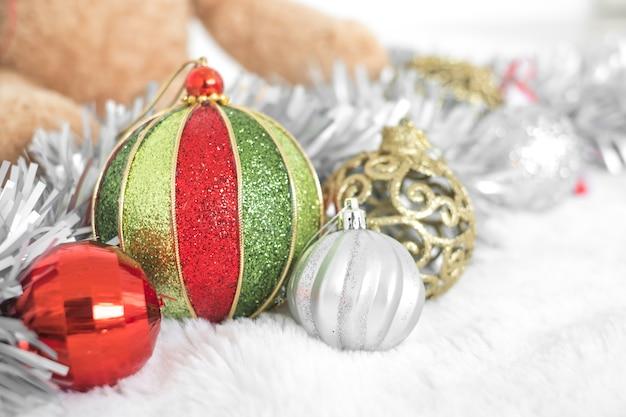 Fundo de natal com um enfeite vermelho, caixa de presente de ouro, bagas e abeto na neve