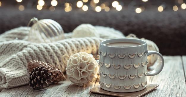 Fundo de natal com uma bela xícara e detalhes de decoração em um fundo desfocado com bokeh.
