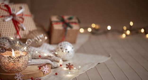 Fundo de natal com vela acesa decorativa prata, luzes e caixas de presente em um fundo desfocado. copie o espaço.