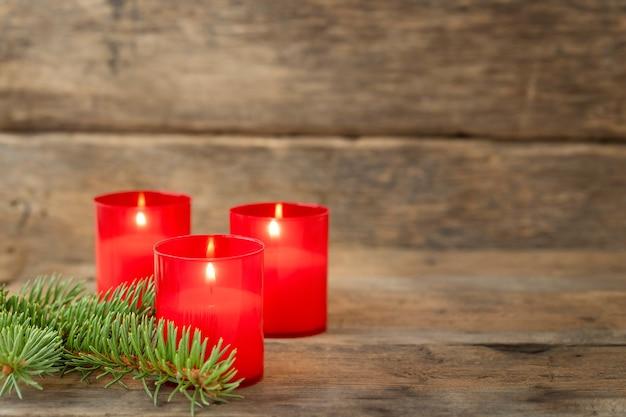 Fundo de natal com velas vermelhas na superfície de madeira