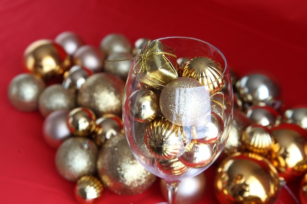 Fundo de natal com vidro de videira e decorações de natal de ouro dentro dele. copo de videira com enfeites de natal