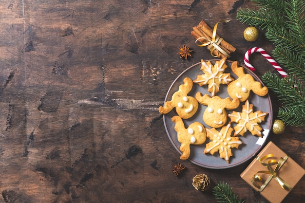 Fundo de natal. composição de natal com ramos de pinheiro, presentes, doces, biscoitos, canela em um fundo escuro de madeira