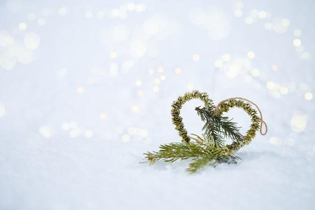 Fundo de natal coração feito de abeto na neve com bokeh