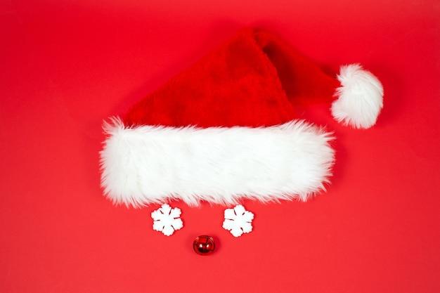Fundo de natal criativo com chapéu de natal e óculos engraçados em um fundo vermelho.